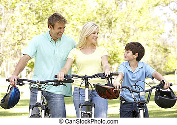 Parents And Son On Cycle Ride In Park