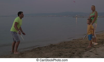 Parents and son paying tennis on the beach