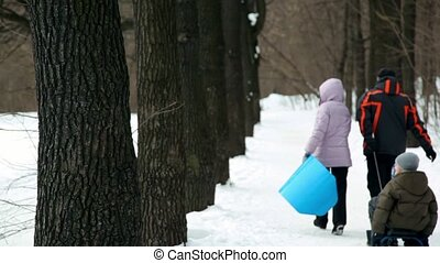 Parents and their children on sled walk by park alley at...