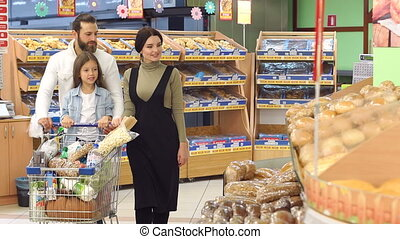 Parents and their cute little daughter while choosing baking in the supermarket.