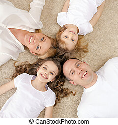 parents and two girls lying on floor at home - family,...