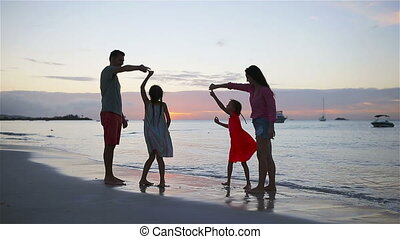 Parents and two kids have a lot of fun on the beach at...