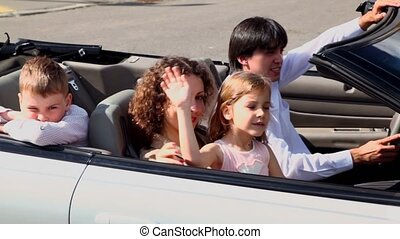 Parents and two kids pass by in cabriolet at sunny day