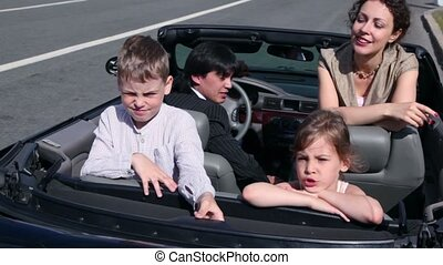 Parents and two kids seat in car and ride away at sunny day