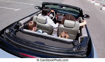 Parents and two kids sit in cabriolet and ride by road, view...