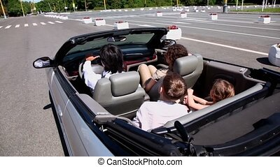 Parents and two kids sit in cabriolet and ride by road
