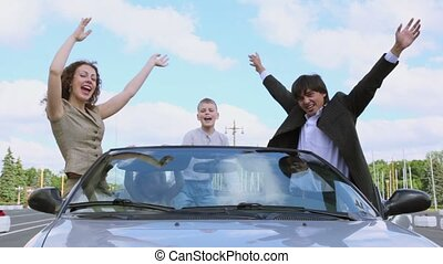 Parents and two kids stand in cabriolet and wave hands