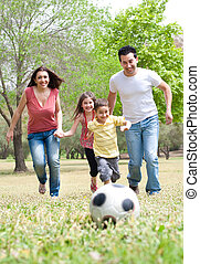 Parents and two young children playing soccer in the green field, outdoor
