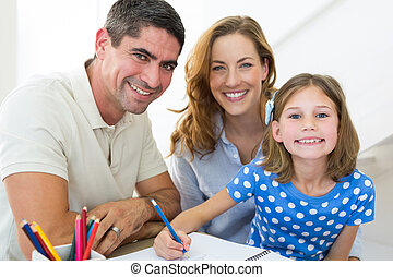 Parents assisting daughter in coloring at home