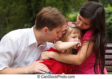 Parents calm crying girl on walk in summer garden. Mum...