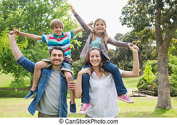 Parents carrying kids on shoulders at park - Portrait of...