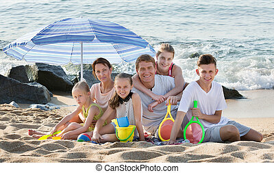 Parents children under sun umbrella - Cheerful parents with ...