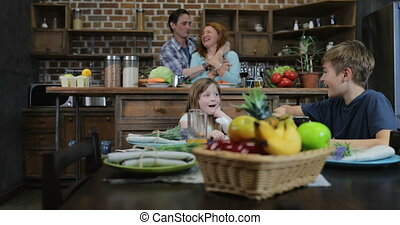 Parents Cooking Meal While Children Eat Sitting At Table Use...