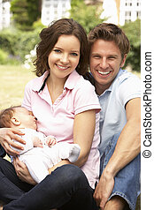 Parents Cuddling Newborn Baby Boy Outdoors At Home