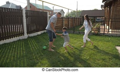 parents enjoy life playing football with active boy on lawn