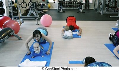 Parents exercising with babies in gym with personal trainer.