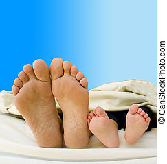 The feet of a young family rest with their new born child, their feet overlap their bed.