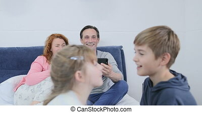Parents Filming Video Of Children Playing Together Sitting On Bed In Bedroom, Happy Family Spending Time Together