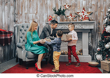 Parents giving Christmas gift to their little son