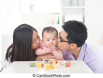 Parents giving their baby daughter a kiss attack.