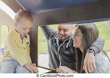 Parents having fun with their child in park playground