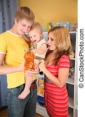parents hold child on hands in playroom
