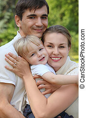 parents hold child on hands outdoor in summer