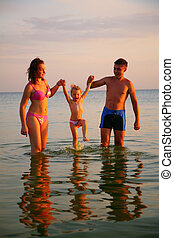 Parents hold daughter for hands in sea