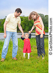 Parents hold for hands of child going on grass