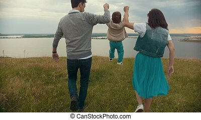 Parents hold their son's hands and raise, the baby jumps, cloudy
