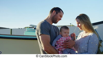 Parents holding baby boy at backyard 4k - Parents holding...