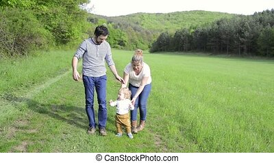Parents holding their little son doing first steps - Mother...