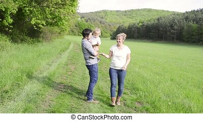 Parents holding with their little son on a walk in nature.