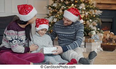 Parents in New Year hats giving present to happy little boy on Christmas eve at home