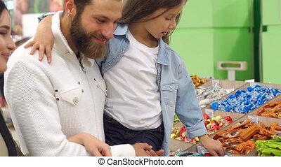 parents, jeune, leur, bonbon, fille, supermarket., achat