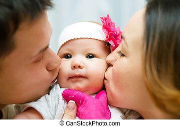 Parents kiss baby