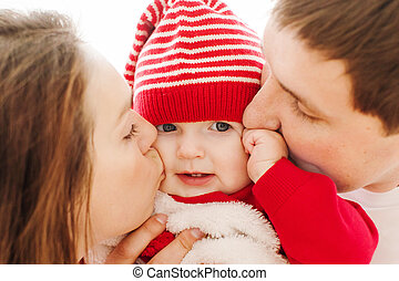 Parents kissing baby in cheeks