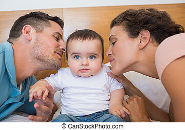 Parents kissing baby on cheek - Loving parents kissing baby...