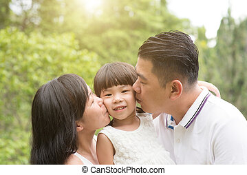Parents kissing child at outdoor park