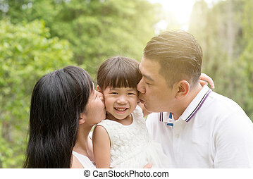 Parents kissing child outdoors