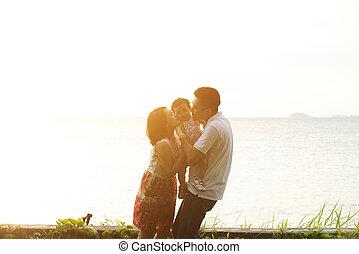 Parents kissing kid on beach sunset