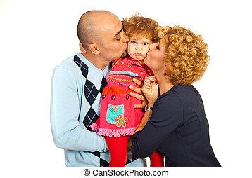 Parents kissing pouting daughter