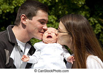 parents kissing their daughter