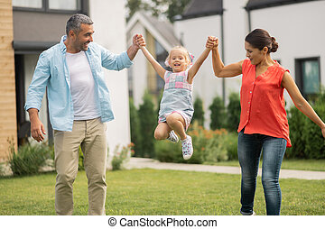 Parents lifting their lovely funny daughter outside near house