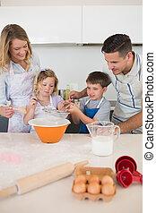 Parents looking at children baking cookies