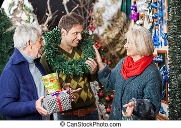 Parents Looking At Son With Wreath Around Neck In Store