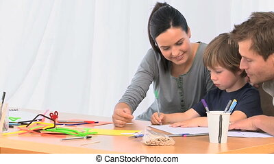 Parents looking at their son drawing