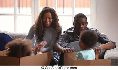 Parents looking how kids hides inside jump out of box