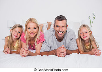 Parents lying in bed with their children