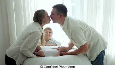 parents mother and father kiss newborn son lying on the bed
